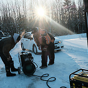 Fabian Blackhawk (left) and Chad Henry with a compressor being used to power an impact wrench as they struggle to remove a flat tire from a grader at the Ochiichagwe'Babigo'Ining Ojibway Nation reserve (also known as the Dalles First Nation) in Northern Ontario, Canada on 15 December 2016.