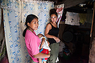 Vilma Tacuyo, 20, shows UK celebrity Myleene Klass around her tiny home while holding her youngest child, Ulderico (10 months), in their one room home in an urban slum in Paranaque City, Metro Manila, The Philippines on 18 January 2013. Vilma had raised her first 3 children on formula and had to cut down on food for her family to afford it. Both John Ashley, 4, and Justin, 3, are malnourished and stunted, and after losing one of her children, she now breastfeeds her youngest, Ulderico. Photo by Suzanne Lee for Save the Children UK