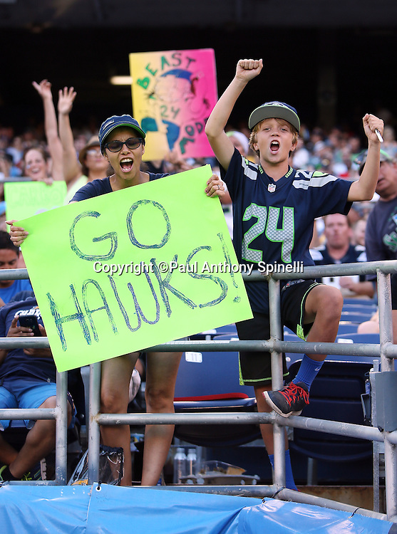 """A pair of Seattle Seahawks fans wave, cheer, and hold up a """"Go Hawks"""" sign during the 2015 NFL preseason football game against the San Diego Chargers on Saturday, Aug. 29, 2015 in San Diego. The Seahawks won the game 16-15. (©Paul Anthony Spinelli)"""