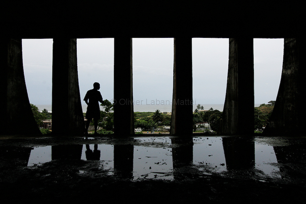 """A man looks out 19 September 2005 over Monrovia from the former uncompleted Ministry of National Defense building in Congo Town on the outskirts of Monrovia. The """"Pentagon"""", named this way by its occupants, shelters 394 families totalling approximately 3,000 people who were booted out in May 2005 of the Barclay Training Center, which had been their home for the last two decades. Former soldiers, who fought for former Liberian presidents Samuel Doe and Charles Taylor, live in this building with no water or electricity, overcoming past differences. The construction of the building started in 1984 under Doe's leadership, and the war interrupted the its completion and later served as a base for Taylor's men."""