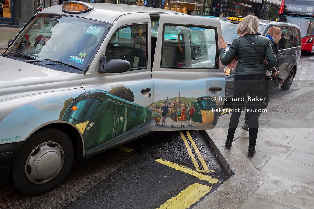 A black cab carrying door advertising for GWR rail travel, stops to drop-off a fare outside the Selfridge's department store on Oxford Street, on 4th March 2019, in London England.