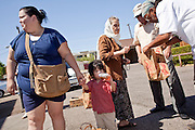 20 JUNE 2009 - PHOENIX, AZ: Mireya Renteria and her son, Ricardo Renteria, 2, wait for the walk in clinic to open while others pick up fresh fruit and vegetables at the Cultural Cup. The walk in clinic at the Cultural Cup Food Bank started two years ago when Cultural Cup founder Zarinah Awad wanted to expand the food bank's outreach and provide basic medical care for the people who use the food bank. The clinic sees, on average, 7 - 11 patients a week. Awad said that as the economy has worsened since the clinic opened and demand has steadily increased. She attributes the growth to people losing their jobs and health insurance. The clinic is staffed by volunteers both in the office and medical staff. Adults are seen every Saturday. Children are seen one Saturday a month, when a pediatrician comes in. Awad, a Moslem, said the food bank and clinic are rooted in the Moslem tradition of Zakat or Alms Giving, the giving of a small percentage of one's income to charity which is one of the Five Pillars of Islam.   PHOTO BY JACK KURTZ