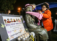 Supporters place a scarf and hat on a memorial statue honoring 'Comfort Women' at Glendale Peace Monument during a candlelight vigil in remembrance and support of 'Comfort Women', Japanese military sexual slavery victims during World War II, on January 5, 2016, in Glendale, California. AFP PHOTO / Ringo Chiu