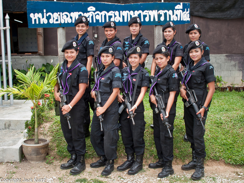 Sept. 29, 2009 -- BAAN TROKBON, THAILAND: Some of the women Rangers pose for a photo in front of their command tent. The 39 women in the 44th Army Ranger Regiment are the only Thai women seeing front line active duty against Moslem insurgents in Thailand's deep south provinces of Pattani, Narathiwat and Yala. All of the other women serving in Thai security services are employed as office and clerical workers. The Ranger women are based at the Ranger camp in the Buddhist village of Baan Trokbon in Sai Buri district of Pattani province. The unit was formed in 2006 after Muslims complained about the way Thai soldiers, all men, treated Muslim women at roadblocks and during security sweeps. The women are frequently called upon to back up Thai regular army units when they are expected to encounter a large number of Muslim women. At least two of the women have been killed by Muslim insurgents. The unit has both Muslim and Buddhist members. Many of the women in the unit joined after either their fathers or husbands were killed by insurgents.    Photo by Jack Kurtz / ZUMA Press