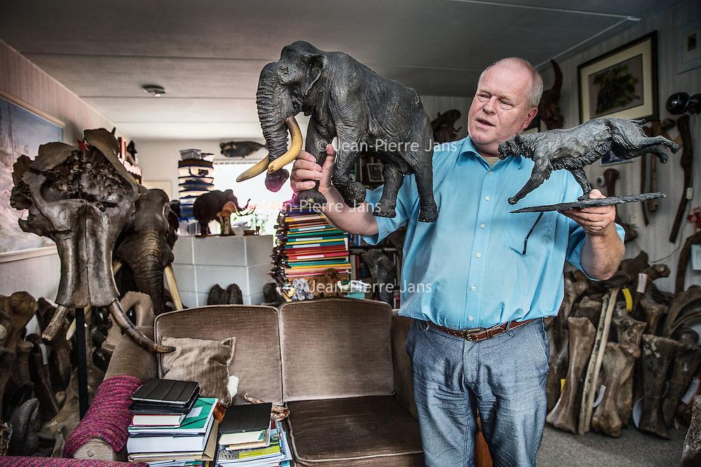 Nederland, Hoofddorp, 21 september 2016.<br /> Dick Mol, de sabeltandkattenexpert toont zijn liefde voor uitgestorven diersoorten zoals de mammoet en de sabeltandkat (r) waarvan hij een mooi beeld van in zijn hand vasthoudt gemaakt door kunstenaar Remie Bakker.<br /> Ook heeft hij fossiele hoektanden van deze kat in zijn verzameling. <br /> <br /> Netherlands, Hoofddorp, September 21, 2016.<br /> Dick Mol, the machairodontinae expert shows his love for extinct animals such as the mammoth and the saber-toothed cat. He also has fang fossil of this cat in his collection. On the right he is showing a model made by artist Remie Bakker. <br /> <br /> Foto: Jean-Pierre Jans