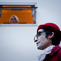 "London, UK - 3 November 2013: Natalia Goncharova (L) looks at her husband Pavel Ivanov (R) from the window of a converted truck used as a changing room. Pavel and Natalia are married and run together the theatre collective of clowns ""Grim Massa""."