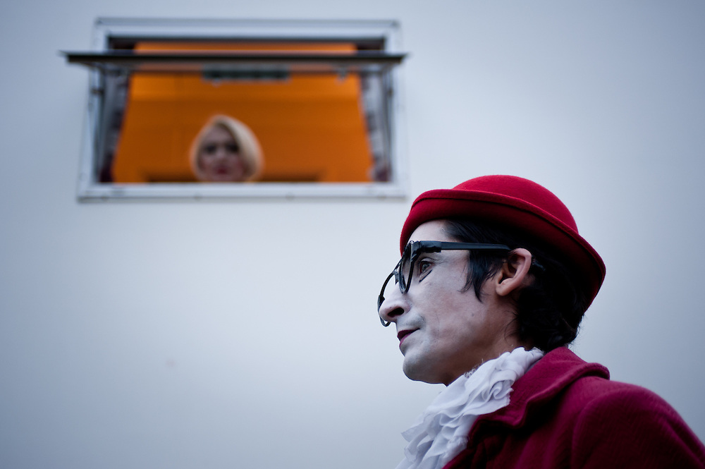 """London, UK - 3 November 2013: Natalia Goncharova (L) looks at her husband Pavel Ivanov (R) from the window of a converted truck used as a changing room. Pavel and Natalia are married and run together the theatre collective of clowns """"Grim Massa""""."""