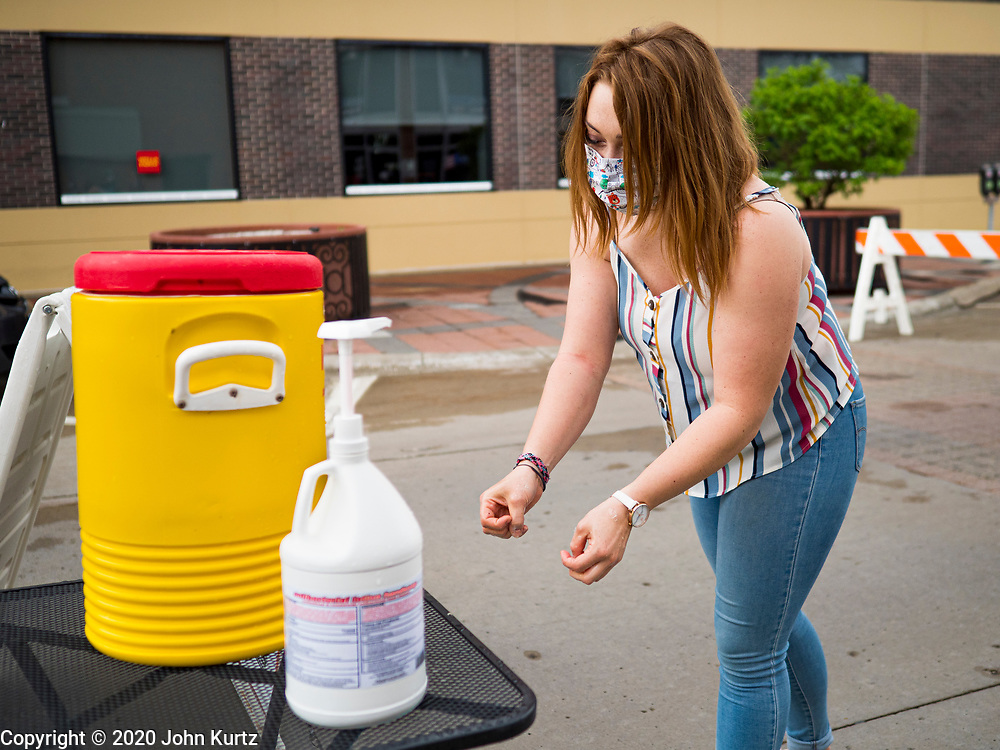 23 MAY 2020 - AMES, IOWA: CLAIRE OKOREN, a 2020 graduate of Iowa State University, shakes water off her hands after washing them at the handwashing station at the entrance to the downtown Farmers' Market in Ames. The Ames Main Street Farmers' Market reopened Saturday after nearly a month of only online sales because of Iowa's bans on large gatherings caused by the COVID-19 pandemic. Only about 15 venders set up stalls Saturday and attendance was significantly lower than normal. All of the venders wore face masks and many, but not all, of the shoppers wore face masks. Farmers' markets are popular community gatherings in Iowa, but they've been on hiatus since the Coronavirus (SARS-CoV-2) pandemic. At this time, Iowa farmers' markets are not allowed to have entertainment or sell non-food or non-agricultural goods.          PHOTO BY JACK KURTZ