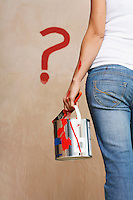 Woman holding painting can facing wall with painted question mark mid section back view