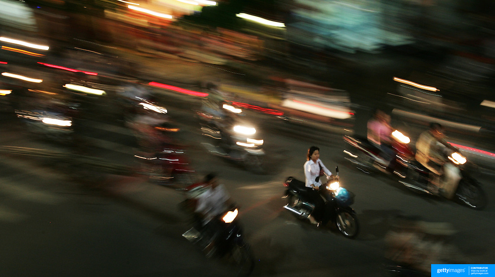 A decade ago Vietnams roads were teaming with bicycles. But as the countries economic growth increased bringing relative affluence to the working class, the push bike has been replaced by the scooter as the main mode of transport for the nations population.. Ho Chi Minh City alone has an estimated three million scooters buzzing around the streets day and night. Everyday life is dominated by the site of the scooter. Street corners have become parking lots for rows upon rows of parked scooters.. Puncture repair workmen wait on every city street to come to the aid of the rider with a blown tyre, and make a quick buck in the process, while families have a night on the town together, all seated on the same scooter!.Any number of items can be seen transported on the back of a scooter, from pigs to wardrobes anything that can be tied down is moved on the trusted scooter..Even in the outlying country areas the scooter is now used to transport produce to and from the markets. While even beach goers at the coastal towns head for a swim and a sunbathe accompanied by their scooter.  .Street Scene, Hanoi, Vietnam on September 29, 2006. Photo Tim Clayton