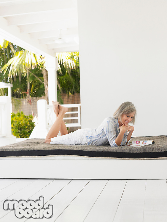 Woman lying down on day bed on verandah