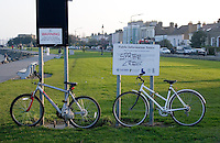 Two bicycles parked at Sandymount Strand in Dublin Ireland on a winters evening. Health notice warning about collecting shellfish on the strand