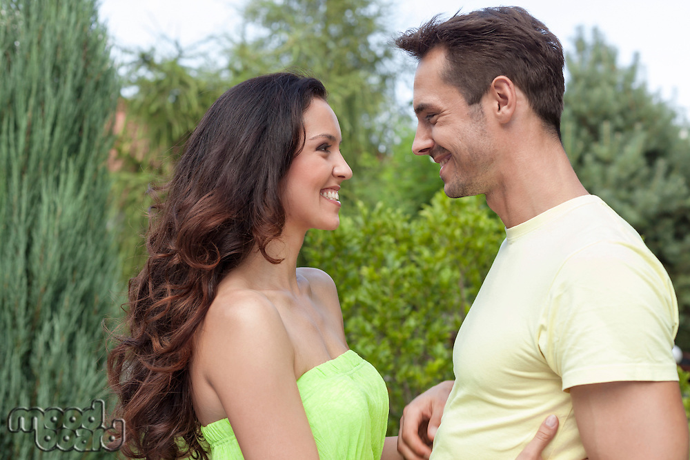 Side view of smiling young couple looking at each other in park
