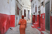 A woman walking in a narrow street where the lower section of the walls is painted red, in the medina or old town of Tetouan on the slopes of Jbel Dersa in the Rif Mountains of Northern Morocco. Tetouan was of particular importance in the Islamic period from the 8th century, when it served as the main point of contact between Morocco and Andalusia. After the Reconquest, the town was rebuilt by Andalusian refugees who had been expelled by the Spanish. The medina of Tetouan dates to the 16th century and was declared a UNESCO World Heritage Site in 1997. Picture by Manuel Cohen