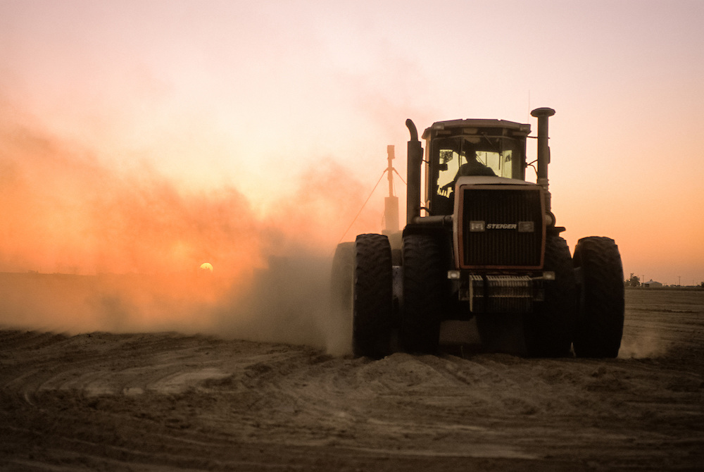 CENTRAL VALLEY, CALIFORNIA - Tractor working ground a sunset with dust cloud