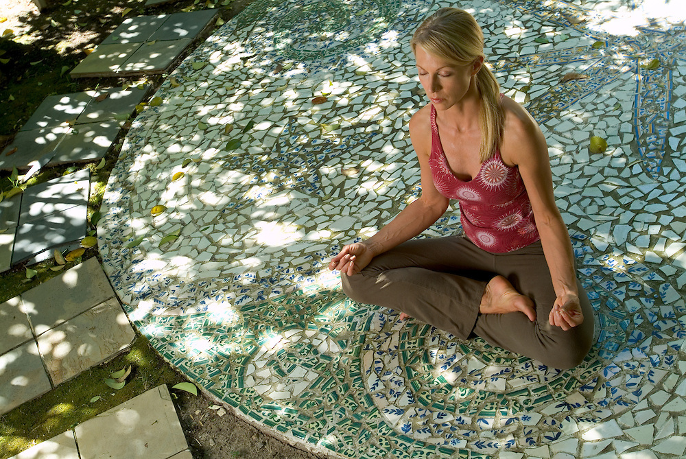 Wellness image of young woman meditating outside on mosaic patio