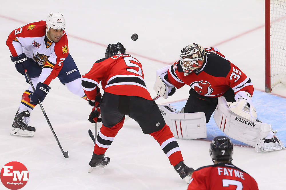 Mar 31, 2014; Newark, NJ, USA; New Jersey Devils goalie Cory Schneider (35) makes a save on Florida Panthers center Scott Gomez (23) while New Jersey Devils defenseman Adam Larsson (5) defends during the third period at Prudential Center. The Devils defeated the Panthers 6-3.