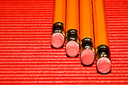 4 yellow pencils with erasers at the tip on a red  corrugated surface