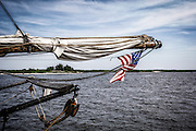 A flag hangs off the bow end from one of the sail masts as it sits dockside on the Maurice River alongside Bayshore Center at Bivalve.