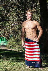 hot shirtless man in an American flag towel outdoors in the park