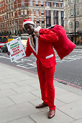 © Licensed to London News Pictures. 11/12/2014. London, UK. Apprentice candidate 2014, Steven Ugoalah dressed as Santa is accompanied by two women dressed as elves from PETA delivers a sack of coal to Harvey Nichols department store in Knightsbridge, London in protest at them selling fur this Christmas. Harvey Nichols previously maintained a fur-free policy for over a decade, but has started selling fur again this year. Photo credit : Vickie Flores/LNP