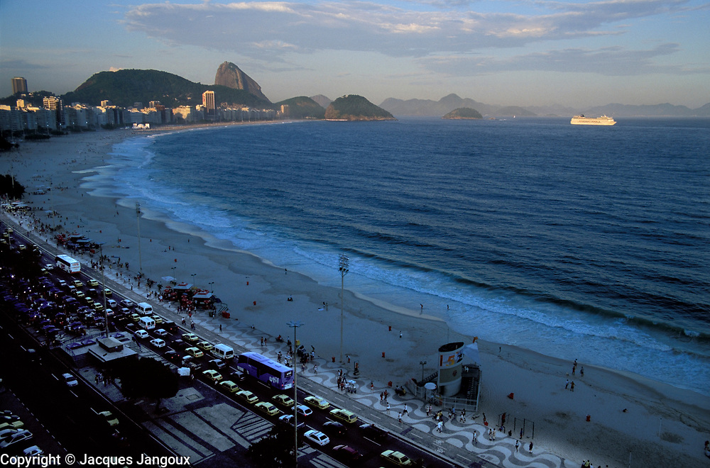 Cruise ship passingin front of Copacabana Beach already in shade in late afternon, with Sugar Loaf in background, Rio de Janeiro, Brazil