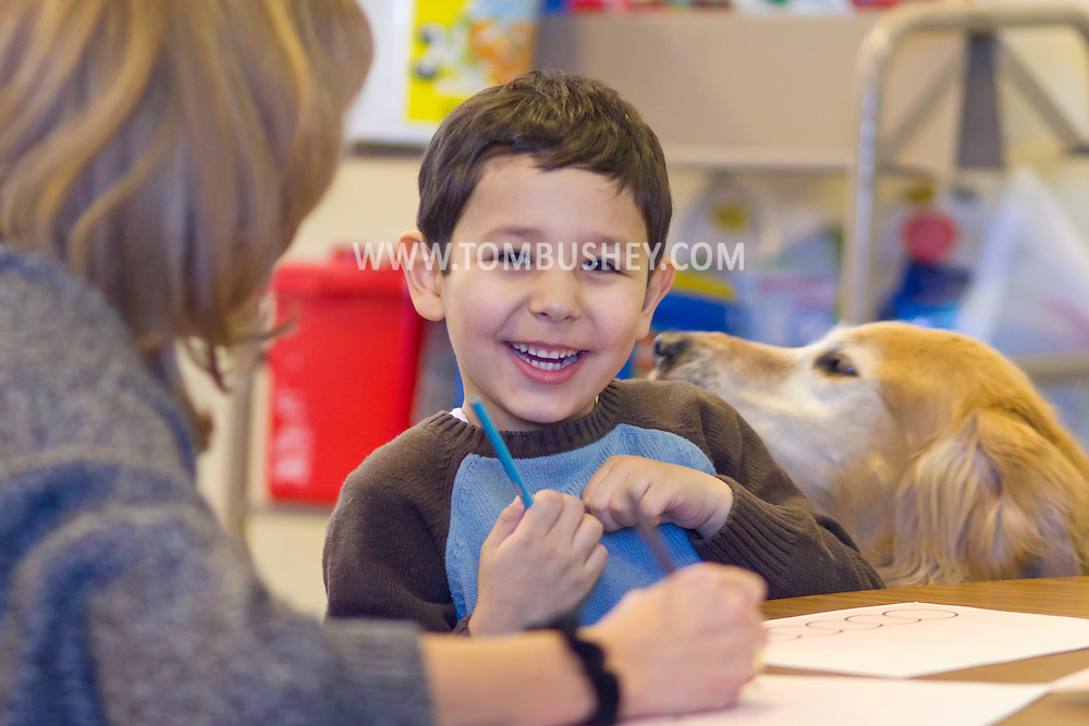 "Middletown, New York - Hope Roach and her therapy dog Lu work with a child during a ""Getting Ready for Kindergarten"" program at Thrall Library on Jan. 30, 2014."