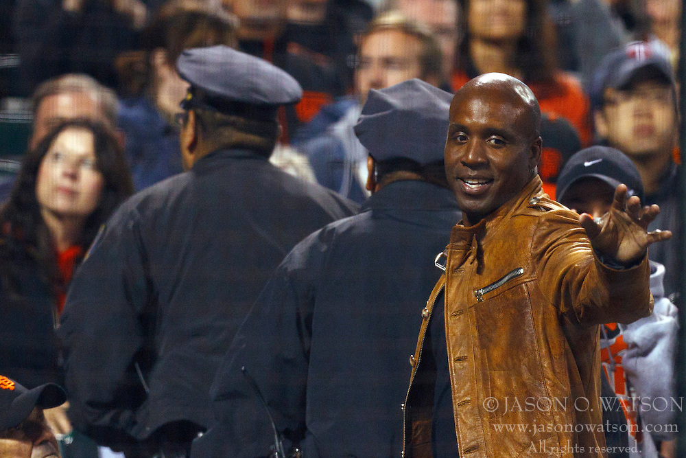 June 22, 2011; San Francisco, CA, USA;  Former San Francisco Giants outfielder Barry Bonds (right) waves to fans while being escorted through the stands by two police officers during the seventh inning between against the Minnesota Twins at AT&T Park.