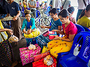 20 NOVEMBER 2017 - YANGON, MYANMAR: A fruit vendor on the Dala Ferry. There are vendors selling fruit, snacks, betel, toys, and phone SIM cards on the ferry. People getting off the Dala Ferry in Yangon leave the ferry terminal. Tens of thousands of commuters ride the ferry every day. It brings workers into Yangon from Dala, a working class community across the river from Yangon. A bridge is being built across the river, downstream from the ferry to make it easier for commuters to get into the city.     PHOTO BY JACK KURTZ