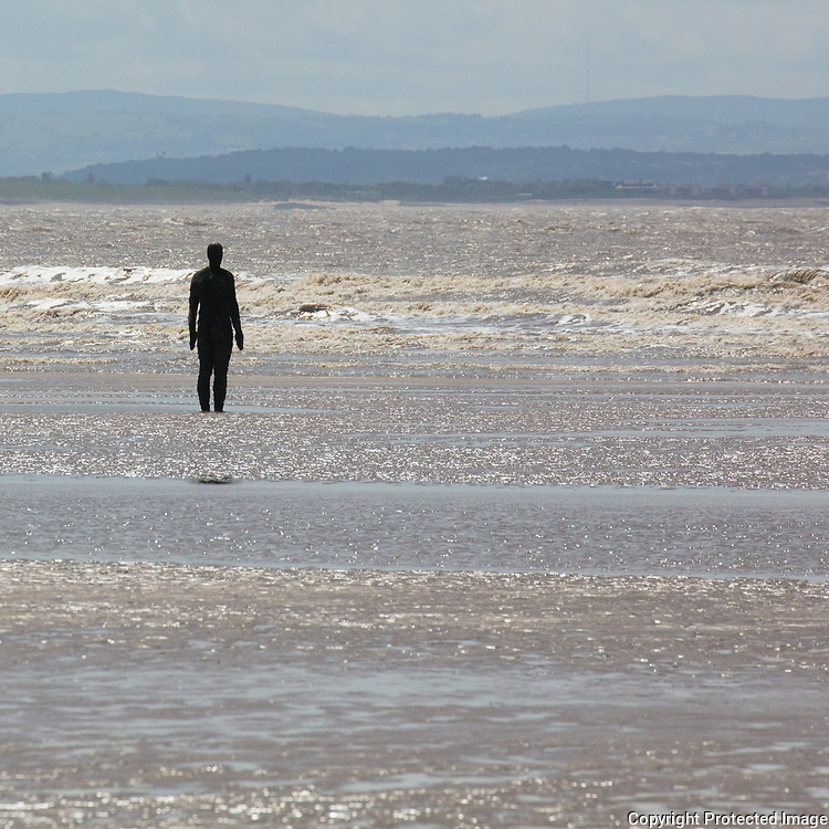 Another Place cast iron figure looks out towards the Irish Sea, Crosby Beach, Merseyside.