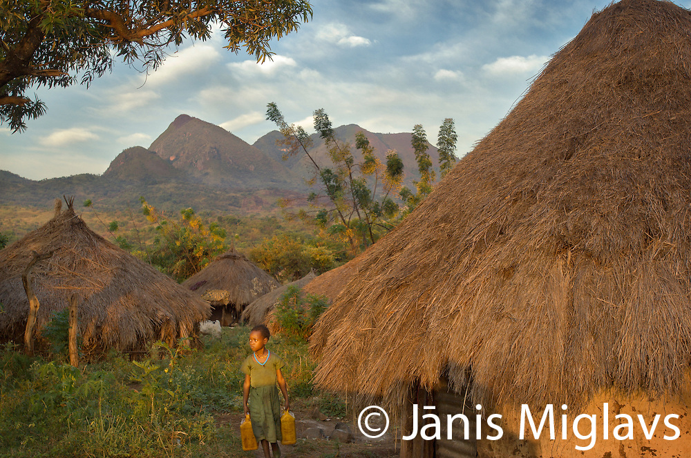 Young girl in green dress carrying water cans past thatch-roofed houses of Suri (Surma) Tribe village of Tulgit in green landscape with mountains in background, Omo region, Ethiopia.