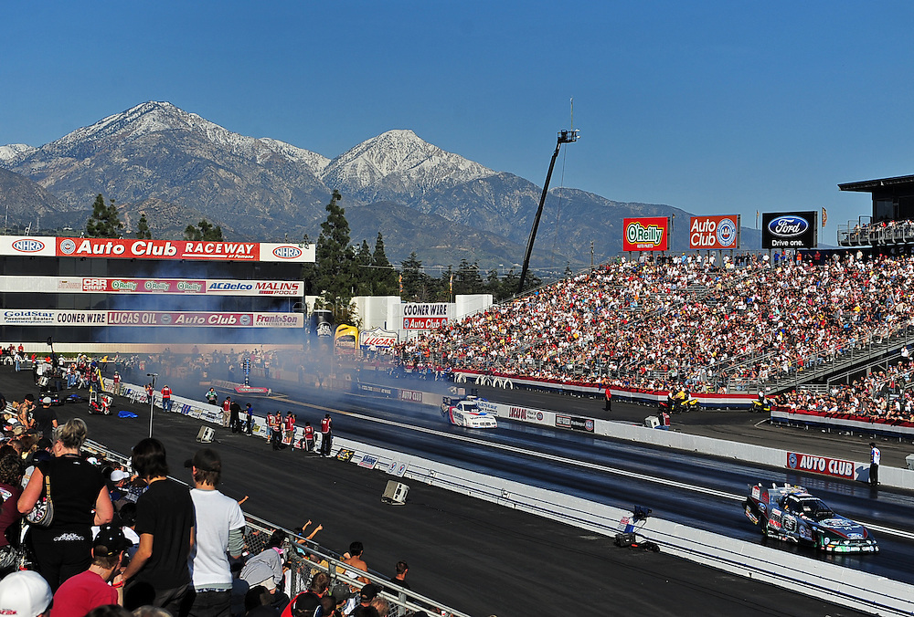 Feb. 14, 2010; Pomona, CA, USA; NHRA funny car driver Jack Beckman (left) and John Force do a burn out during semi finals at the Kragen O'Reilly Winternationals at Auto Club Raceway. Mandatory Credit: Jennifer Stewart-US PRESSWIRE