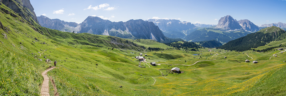 Walk in beautiful Alpe di Seceda by wooden malga (or singular malghe: herders hut), above St. Christina and Ortisei, in Val Gardena, in South Tyrol, the Dolomites, Italy, Europe. In the distance from left to right are the Puez Group, Sella Group, and Langkofel Group (Sassolungo, 3181 meters/10,436 feet, above Ciampinoi and Alpe di Suisi). The beautiful ski resort of Selva di Val Gardena (German: Wolkenstein in Gröden; Ladin: Sëlva Gherdëine) makes a great hiking base in the Trentino-Alto Adige/Südtirol (South Tyrol) region of Italy. For our favorite hike in the Dolomiti, start from Selva with the first morning bus to Ortisei, take the Seceda lift, admire great views up at the cross on the edge of Val di Funes (Villnöss), then walk 12 miles (2000 feet up, 5000 feet down) via the steep pass Furcela Forces De Sieles (Forcella Forces de Sielles) to beautiful Vallunga (trail #2 to 16), finishing where you started in Selva. The hike traverses the Geisler/Odle and Puez Groups from verdant pastures to alpine wonders, all preserved in a vast Nature Park: Parco Naturale Puez-Odle (German: Naturpark Puez-Geisler; Ladin: Parch Natural Pöz-Odles). UNESCO honored the Dolomites as a natural World Heritage Site in 2009. This panorama was stitched from 4 overlapping photos.