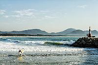 Surfista entrando na água e Farol da Barra da Lagoa. Florianópolis, Santa Catarina, Brasil. / Surfer and Barra da Lagoa Lighthouse. Florianopolis, Santa Catarina, Brazil.