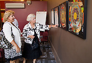 Mary Kay McGrath (from left) and Patty Everist both of Cedar Rapids look over puzzles on display at the CSPS Hall Grand Re-opening in Cedar Rapids on Friday evening, August 26, 2011. About 190 people attended the event which featured a concert by Susan Werner.