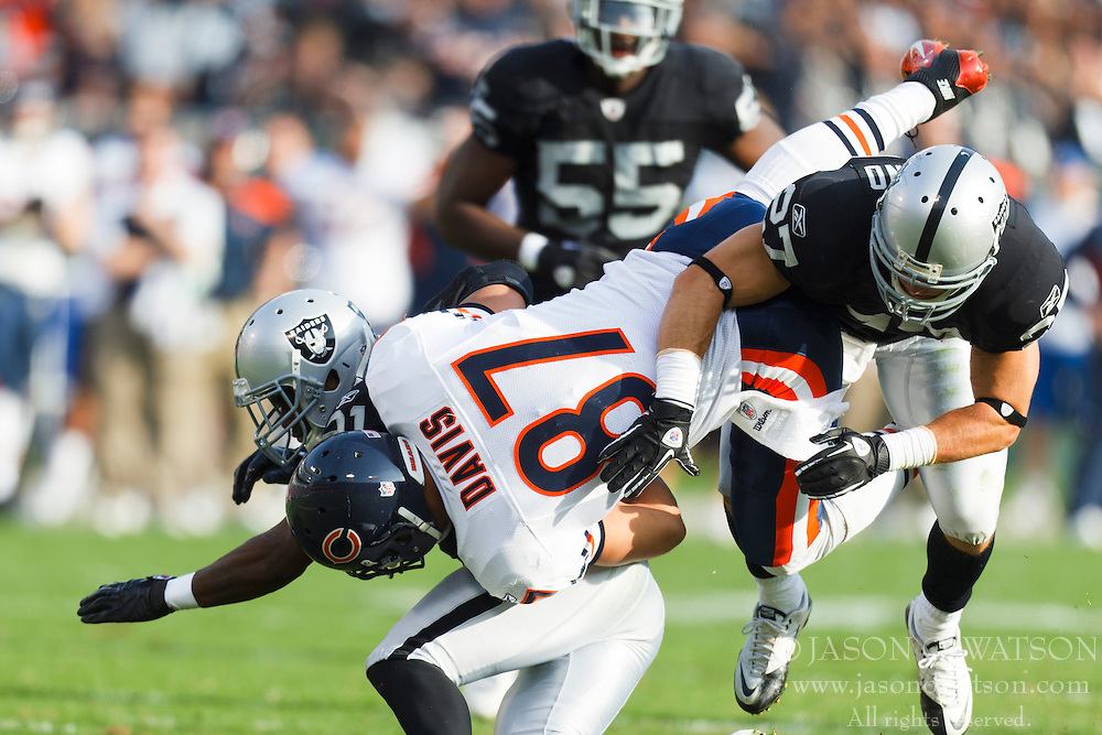Nov 27, 2011; Oakland, CA, USA; Chicago Bears tight end Kellen Davis (87) is tackled by Oakland Raiders cornerback Lito Sheppard (left) and free safety Matt Giordano (right) during the second quarter at O.co Coliseum. Mandatory Credit: Jason O. Watson-US PRESSWIRE