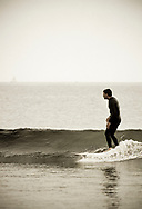 A surfer rides a wave on his longboard in Santa Barbara, California. (releasecode: jk_mr1025) (Model Released)