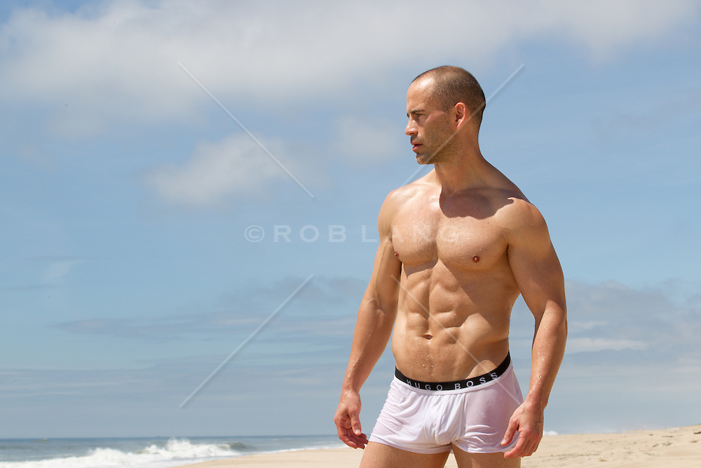 man in wet underwear at the beach