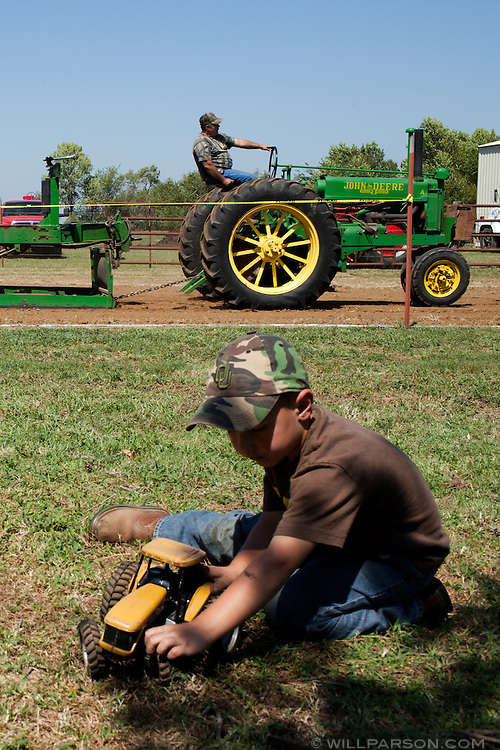 A young spectator plays with a toy tractor during a tractor pull in Girard, Kansas, Sep. 6, 2010.