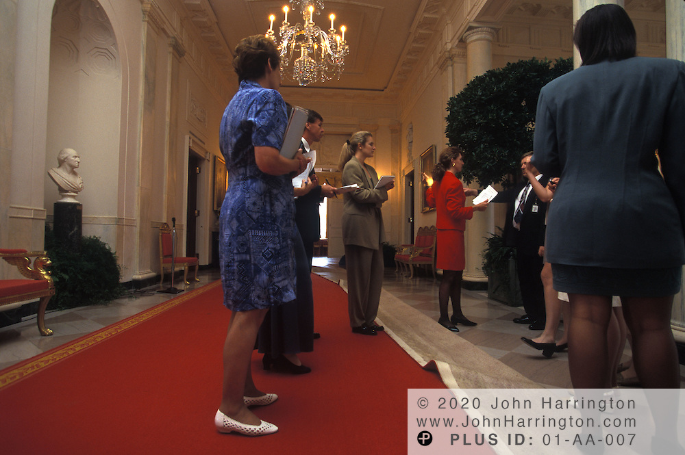 IN THE GRAND FOYER, SOCIAL AIDES RECIEVE THEIR BRIEFING ON THE DETAILS OF THE STATE DINNER.