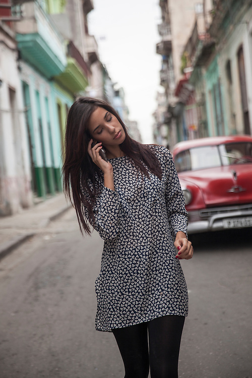 Young woman talks on the phone while walking on a street of Centro Habana, in Havana, Cuba.