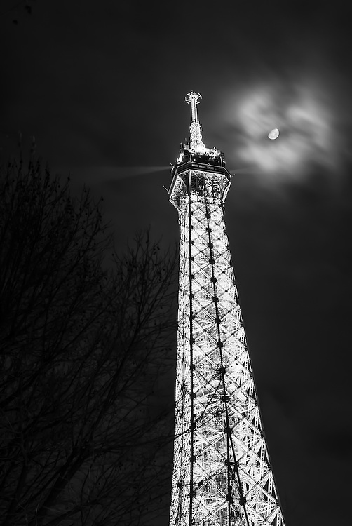 The moon peaks through the clouds above the Eiffel Tower, Paris.