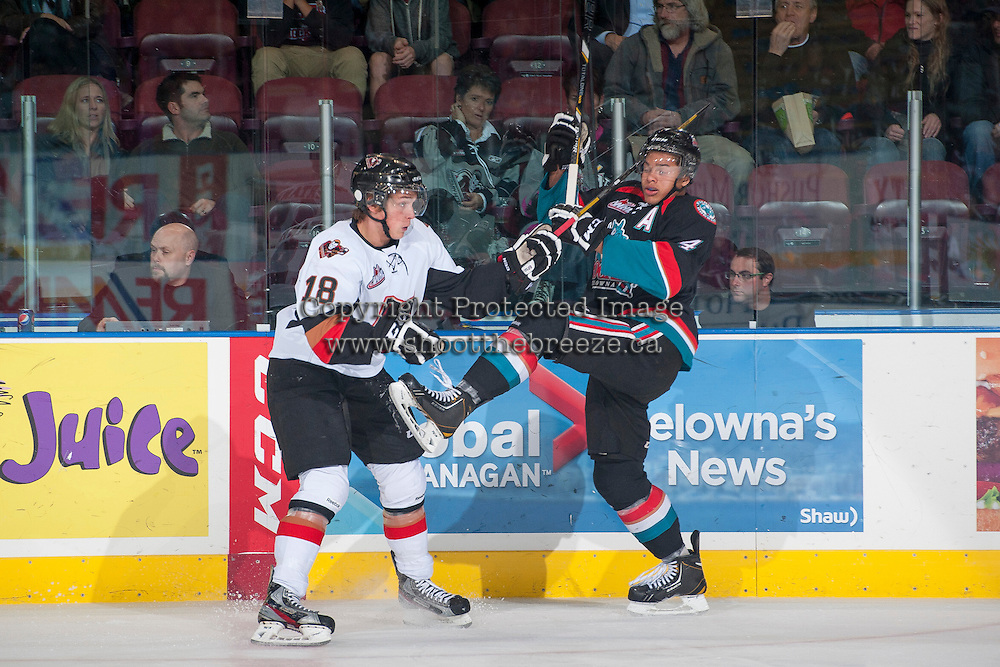 KELOWNA, CANADA - OCTOBER 22: Jake Virtanen #18 of the Calgary Hitmen checks Madison Bowey #4 of the Kelowna Rockets on October 22, 2013 at Prospera Place in Kelowna, British Columbia, Canada.   (Photo by Marissa Baecker/Shoot the Breeze)  ***  Local Caption  ***