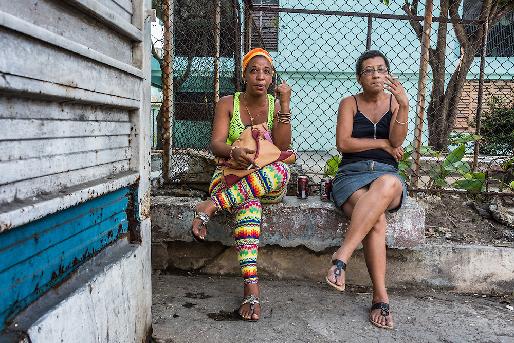 Two women smoke cigarettes and sit on a ledge in identical positions in Havana, Cuba