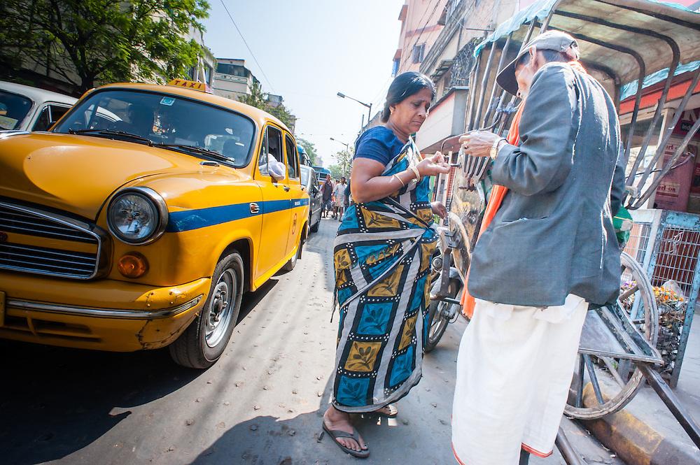 Woman paying rickshaw puller in Kolkata (India).