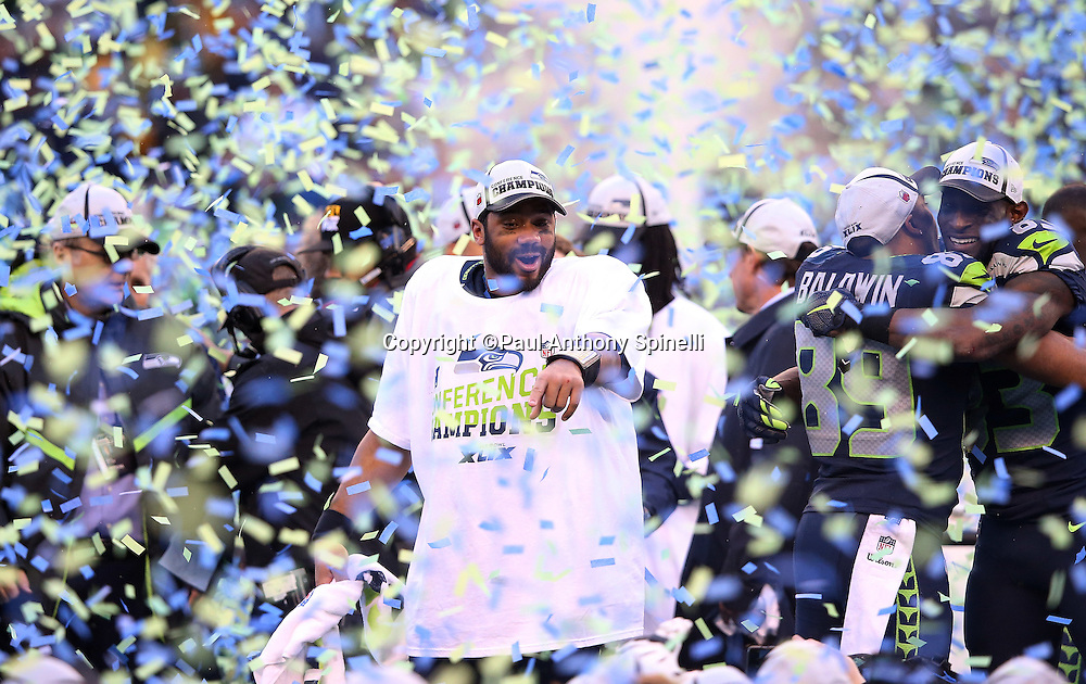 Seattle Seahawks quarterback Russell Wilson (3) points and celebrates as postgame confetti fills the air after the Seattle Seahawks win the NFL week 20 NFC Championship football game against the Green Bay Packers on Sunday, Jan. 18, 2015 in Seattle. The Seahawks won the game 28-22 in overtime. ©Paul Anthony Spinelli