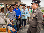 21 FEBRUARY 2014 - KHLONG CHIK, PHRA NAKHON SI AYUTTHAYA, THAILAND:  A Thai police commander talks to farmers protesting against the government on Highway 32. About 10,000 Thai rice farmers, traveling in nearly 1,000 tractors and farm vehicles, blocked Highway 32 near Bang Pa In in Phra Nakhon Si Ayutthaya province. The farmers were traveling to the airport in Bangkok to protest against the government because they haven't been paid for rice the government bought from them last year. The farmers turned around and went home after they met with government officials who promised to pay the farmers next week. This is the latest blow to the government of Yingluck Shinawatra which is confronting protests led by anti-government groups, legal challenges from the anti-corruption commission and expanding protests from farmers who haven't been paid for rice the government bought.   PHOTO BY JACK KURTZ