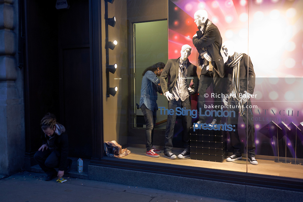 Window dresser adjusting fashion mannequins while man reaches for tobacco on street pavement.