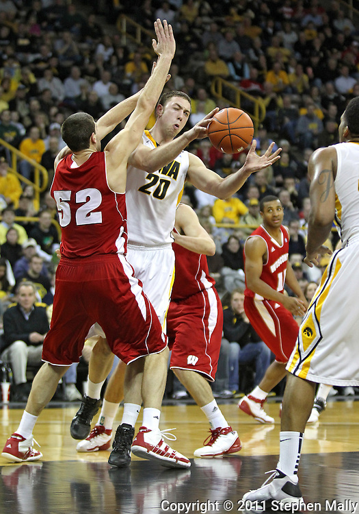 February 09 2011: Iowa Hawkeyes forward Andrew Brommer (20) passes to Iowa Hawkeyes forward Jarryd Cole (50) as Wisconsin Badgers forward Keaton Nankivil (52) defends during the second half of an NCAA college basketball game at Carver-Hawkeye Arena in Iowa City, Iowa on February 9, 2011. Wisconsin defeated Iowa 62-59.
