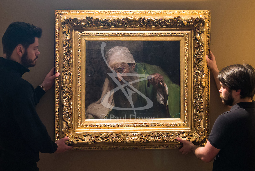 """Bonhams, Mayfair, London, February 26th 2016. Gallery technicians hang Joaquin Soralla y Basitda's """"Un Hebreo"""", estimated to fetch between £300,000-500,000 which will be on display until the Bonhams 19th Century Art Sale in Mayfair, London on march 2nd 2016. ///FOR LICENCING CONTACT: paul@pauldaveycreative.co.uk TEL:+44 (0) 7966 016 296 or +44 (0) 20 8969 6875. ©2015 Paul R Davey. All rights reserved."""